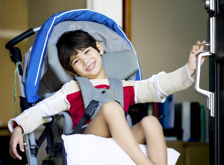 Jaren Jai Wicklund| Handsome four-year-old boy in wheelchair opening the door