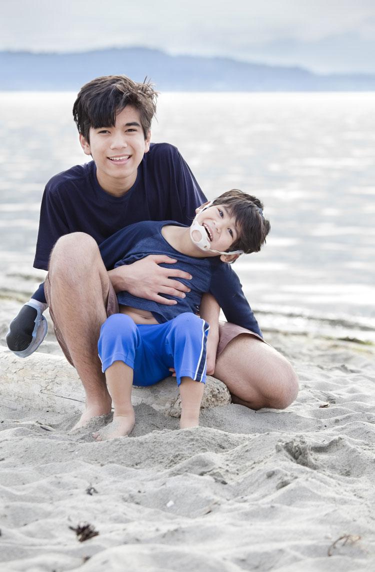 Jaren Jai Wicklund|Big brother holding disabled boy on beach