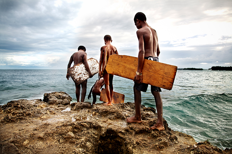 Brian Hodges| Rear view of young boys with surfboards at the shore in Papua New Guinea