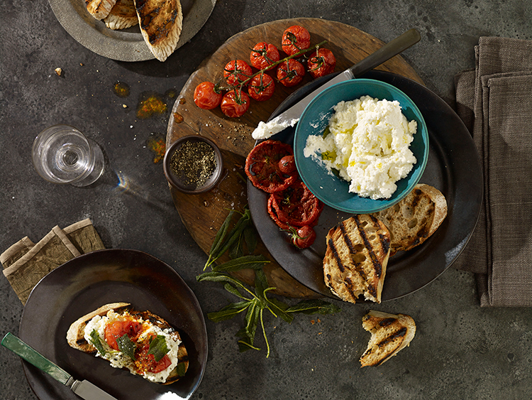 Penny De Los Santos|Top view of bruschetta with creme fraiche, roasted tomato, and sage