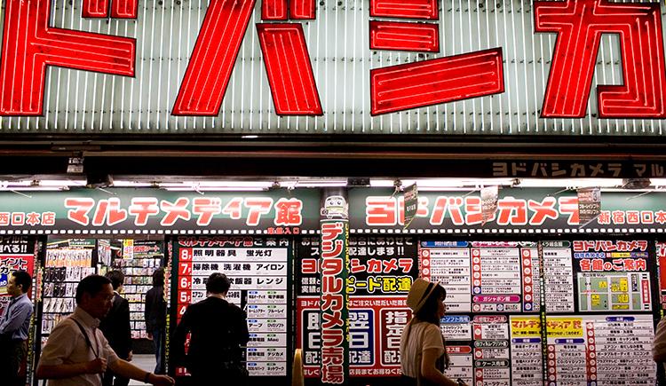 Tokyo, Japan, June 21, 2010: People walking by a store by Alex Federowicz.